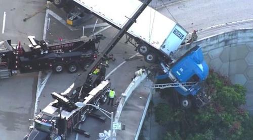 Truck driver hangs over ledge